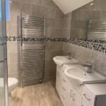 Double sink in bathroom vanity unti and towel rail heater inset mirror in bathroom installation
